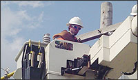 Man with a hard hat in a crane fixing an electric pole